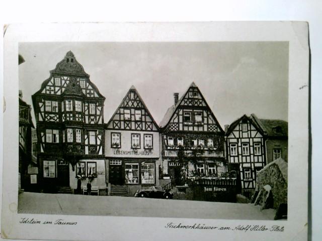AK Idstein im Taunus. Fachwerkhäuser am Adolf Hitler Platz. Gebäudeansicht, Straßenpartie, Auto, Passanten, Lebensmittelhaus, Gasthaus